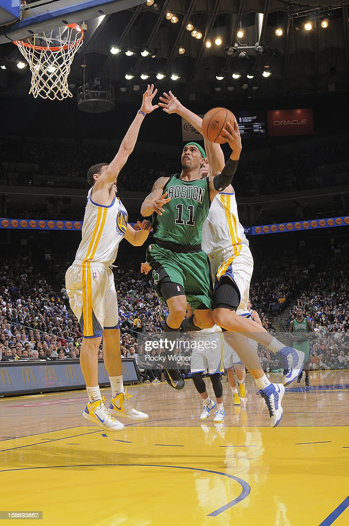 Courtney Lee #11 of the Boston Celtics goes up for the shot against Klay Thompson #11 and Andris Biedrins #15 of the Golden State Warriors on December 29, 2012 at Oracle Arena in Oakland, California.