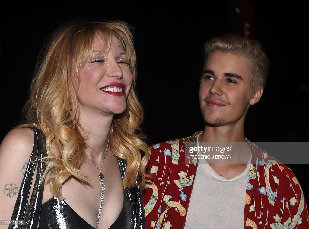 Courtney Love and Justin Bieber attend the Yves Saint Laurent men's fall line and the first part of its women's collection fashion show at the Paladium, in Hollywood, California, February 10, 2016. / AFP / FREDERIC J BROWN