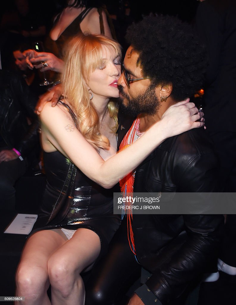 Courtney Love (L) greets Lenny Kravitz at the Yves Saint Laurent men's fall line and the first part of its women's collection fashion show at the Paladium, in Hollywood, California, February 10, 2016. / AFP / FREDERIC J BROWN