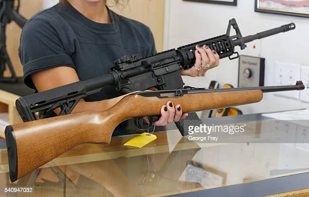 Courtney Manwaring holds an AR15 and a Ruger 1022 both semiautomatic guns at Action Target on June 17 2016 in Springville Utah Semiautomatics are in...