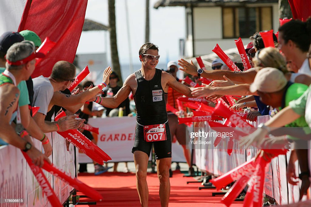 Courtney Ogden of Australia celebrates with fans before crossing the finish line to win the Meta Man Iron Distance Triathlon on August 31, 2013 in Bintan Island, Indonesia.
