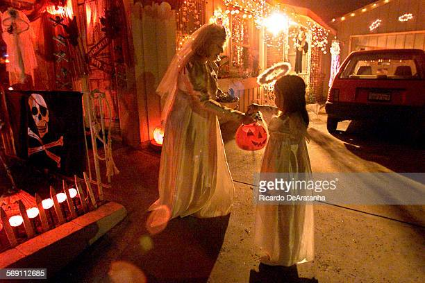 Courtney Springer left giving candy to trick or treater Kylie Valencia of Ventura on Halloween night on Dean Drive in Ventura