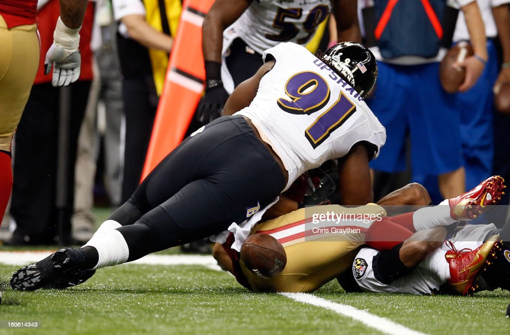 <a gi-track='captionPersonalityLinkClicked' href=/galleries/search?phrase=Courtney+Upshaw&family=editorial&specificpeople=6678836 ng-click='$event.stopPropagation()'>Courtney Upshaw</a> #91 of the Baltimore Ravens forces a fumble from <a gi-track='captionPersonalityLinkClicked' href=/galleries/search?phrase=LaMichael+James&family=editorial&specificpeople=5532594 ng-click='$event.stopPropagation()'>LaMichael James</a> #23 of the San Francisco 49ers in the second quarter during Super Bowl XLVII at the Mercedes-Benz Superdome on February 3, 2013 in New Orleans, Louisiana.