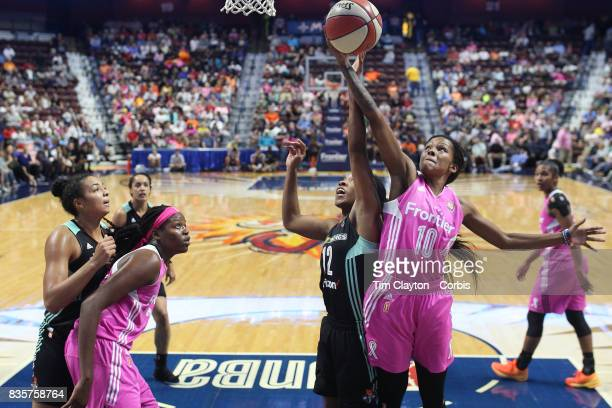 Courtney Williams of the Connecticut Sun rebounds while challenged by Lindsay Allen of the New York Liberty during the Connecticut Sun Vs New York...