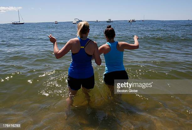 Cousins Stephanie Paradiso of Arlington Va left and Lauren Paradiso of Boston link arms and walk into the ocean after finishing the 41st Falmouth...