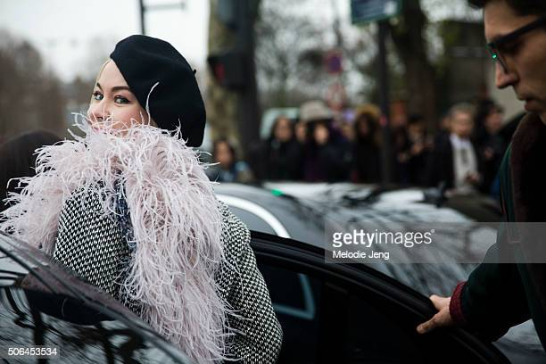 Couture designer Ulyana Sergeenko enters her car in a black beret black and white coat with a feather boa on January 23 2016 in Paris France