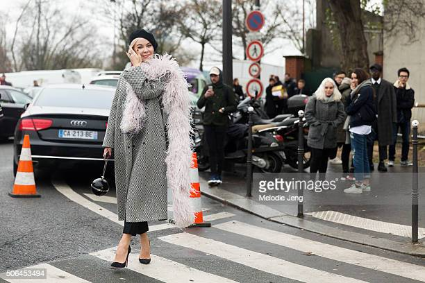 Couture designer Ulyana Sergeenko wears a black beret black and white coat with a feather boa on January 23 2016 in Paris France