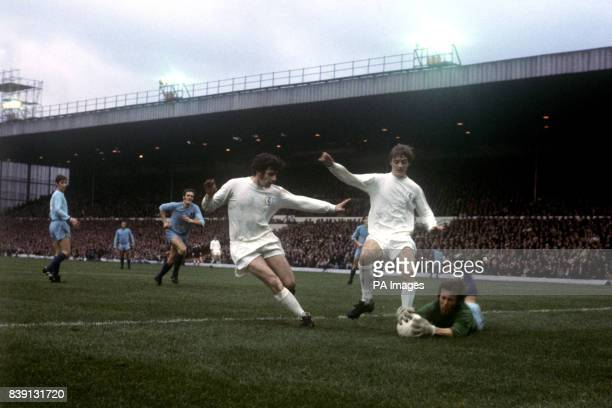 Coventry City goalkeeper Bill Glazier makes a daring save at the feet of the Leeds United's Johnny Giles and Allan Clarke
