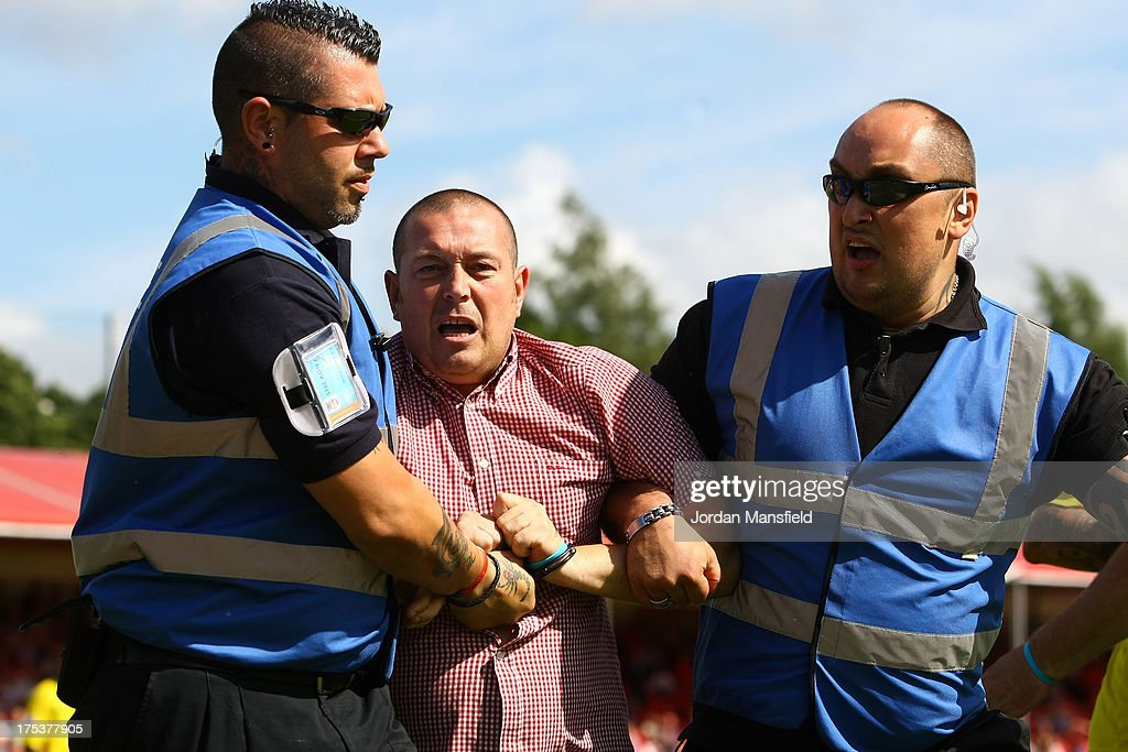 A Coventry City supporter is restrained by security after a pitch-invasion during the Sky Bet League One match between Crawley Town FC and Coventry at Broadfield Stadium on August 03, 2013 in Crawley, West Sussex,