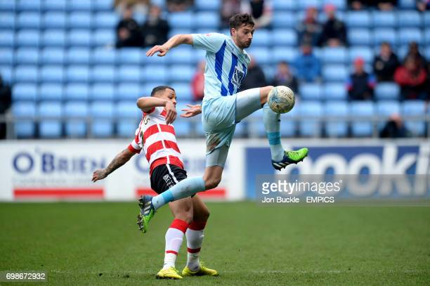 Coventry City's Aaron Martin wins the ball in front of Doncaster Rovers' Jonson ClarkeHarris