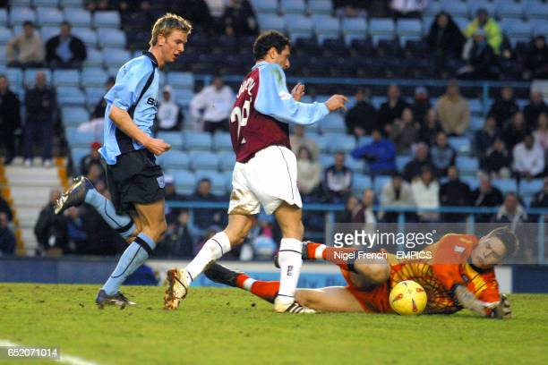 Coventry City's goalkeeper Morten Hyldgaard saves at the feet of Burnley's Dimitrios Papadopoulos