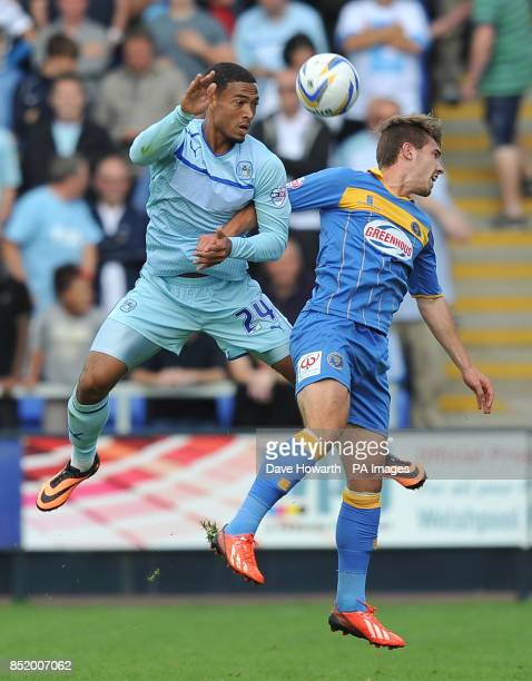 Coventry City's Jordan Clarke and Shrewsbury Town's Tom Bradshaw jump for the ball during the Sky Bet Football League One match at the Greenhous...