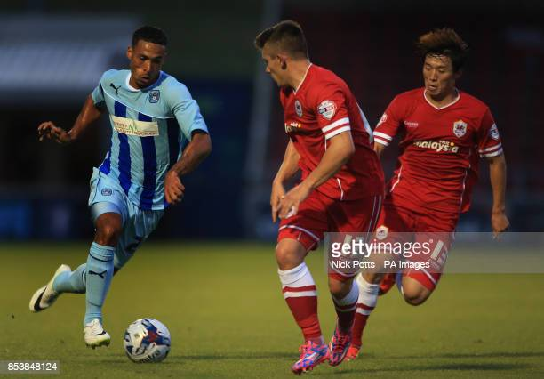 Coventry City's Jordan Clarke runs Cardiff City's pair Declan John and Kim BoKyung during the Capital One Cup First Round match at Sixfields Stadium...