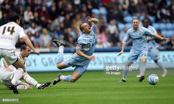Coventry's Michael Doyle is tripped by Hull's Damien Delaney during the CocaCola Football League Championship match at Ricoh Arena Coventry