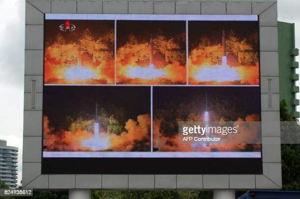 Coverage of an ICBM missile test is displayed on a screen in a public square in Pyongyang on July 29 2017 Kim JongUn boasted of North Korea's ability...