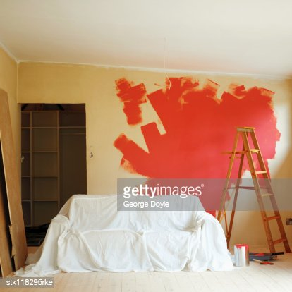Covered couch with a ladder and wall half painted