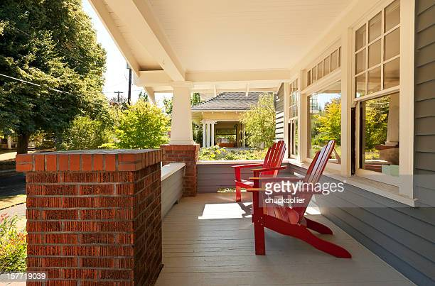 Covered front porch with two red wood chairs