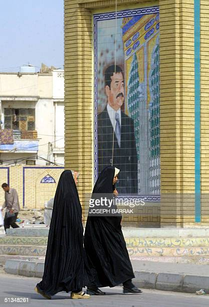 Covered Iraqi Muslim women walk past a mural of their leader Saddam Hussein 11 November 2002 in Baghdad Iraq's parliament is to meet later today in...