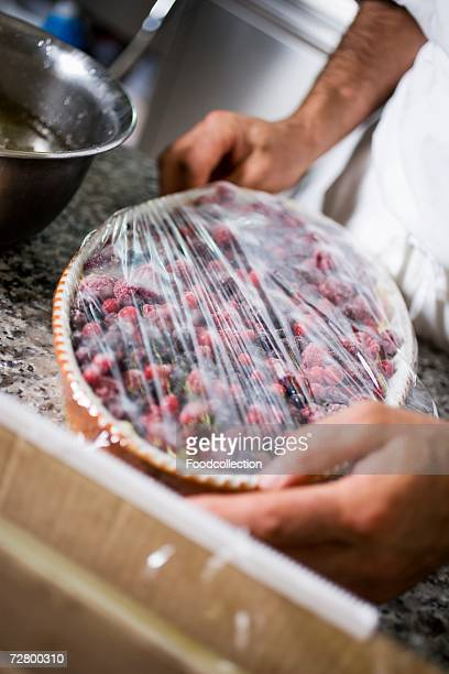 Covering berry dessert with cling film