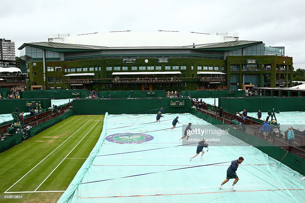 Covers on the outside courts are taken off due a stop in rain on day three of the Wimbledon Lawn Tennis Championships at the All England Lawn Tennis and Croquet Club on June 29, 2016 in London, England.