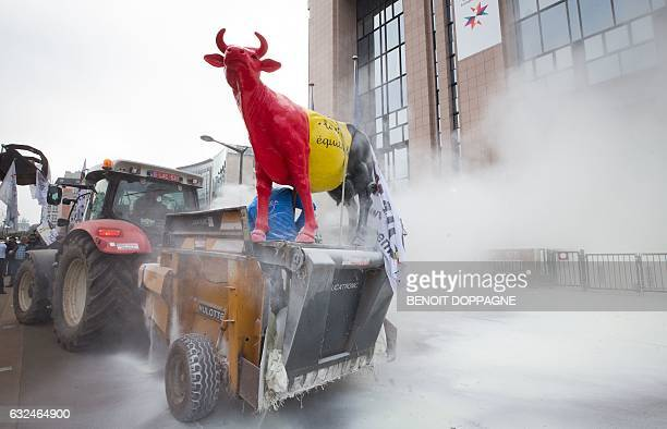 A cow statue stands in front of the European Council main entrance as European Milk board representatives spray milk powder in front of the European...