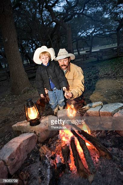 Cowboy and boy by fire