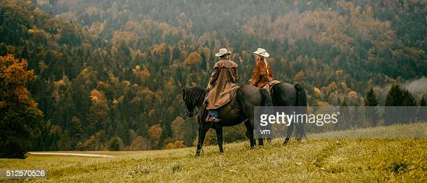 Cowboy and cowgirl riding across a meadow