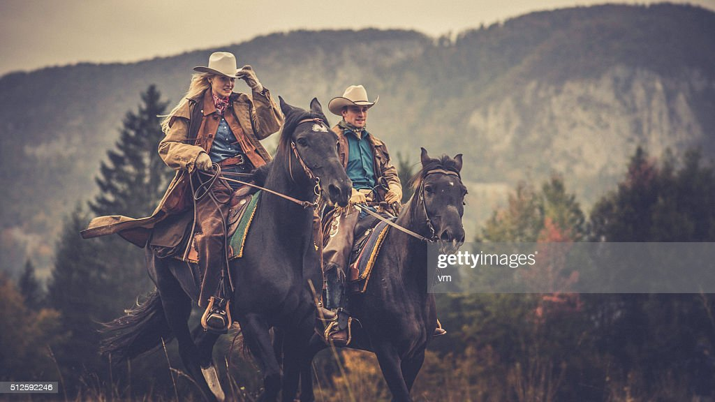 Cowboy and cowgirl riding on horses through the woods : Stock Photo