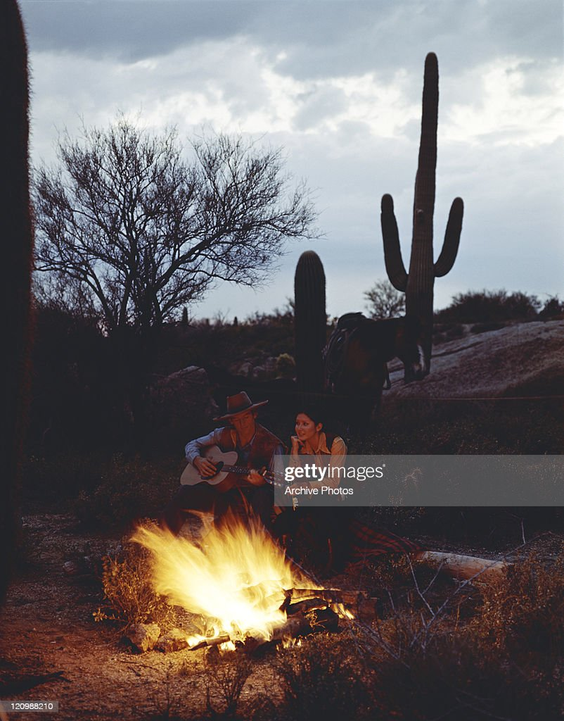 Cowboy and girl sitting beside camp fire : Unknown