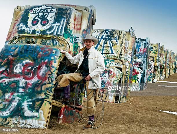 Cowboy at the funky Cadillac Ranch US Route 66 Amarillo Texas