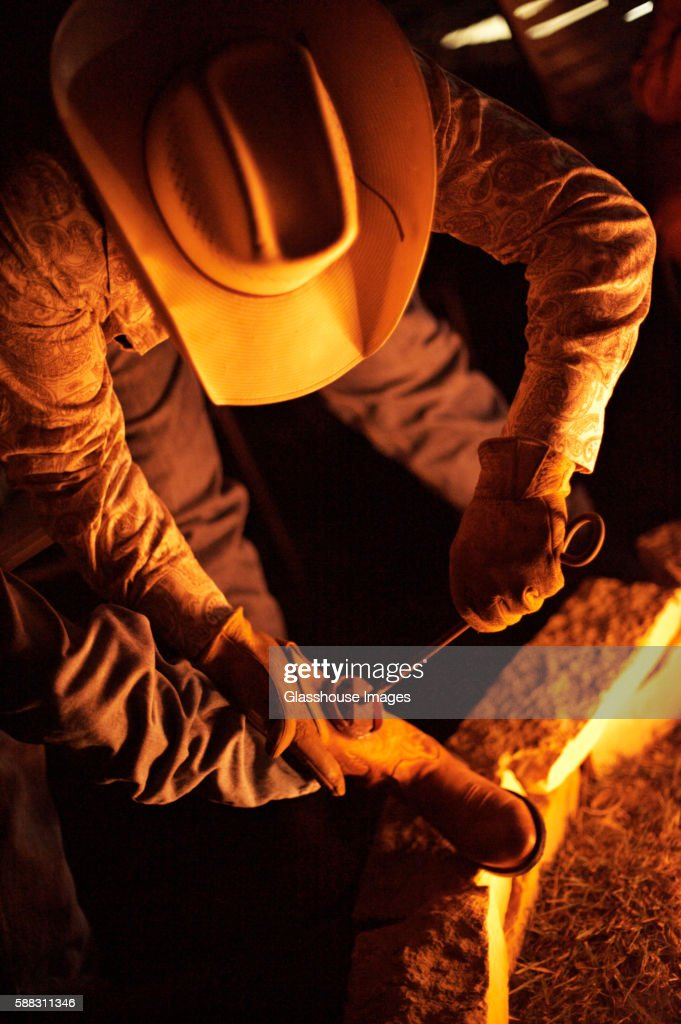 Cowboy Boots Being Branded with Branding Iron