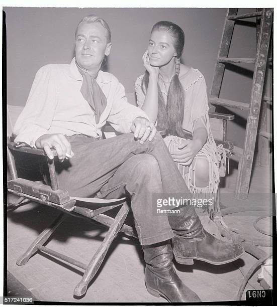 Cowboy costumed Alan Ladd watches with Marissa Pavan while the set is readied for the filming of Drum Beat Marissa who plays an Indian maid in the...