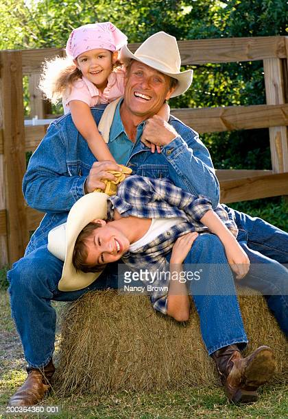 Cowboy father and children (4-9) sitting on hay stack in barn