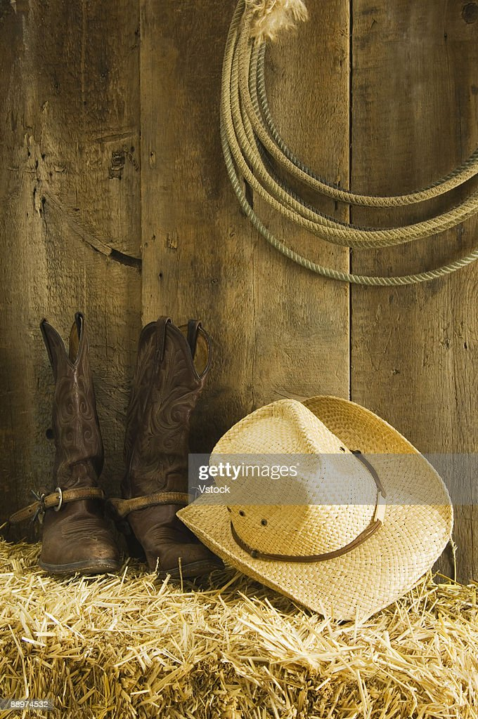 Cowboy hat and boots on hay in barn