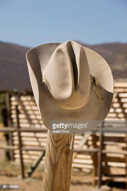 A cowboy hat hanging on a fence