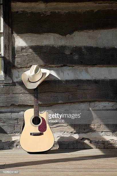 Cowboy hat on guitar leaning on log cabin