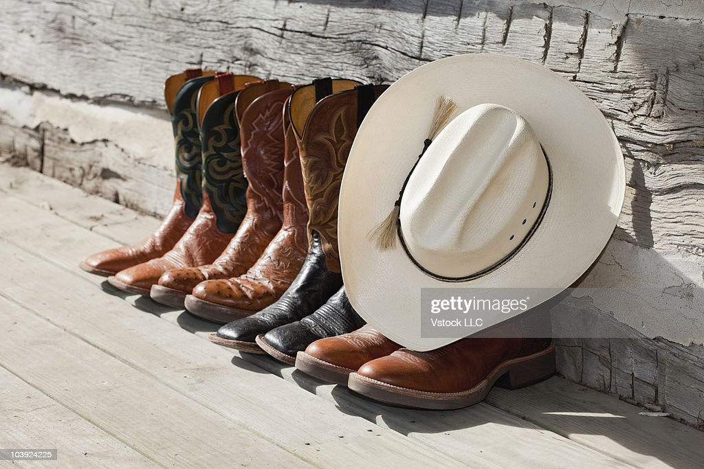 Cowboy hat on row of cowboy boots outside a log cabin