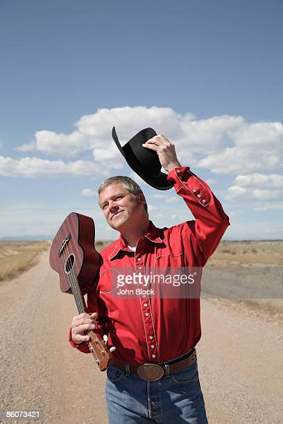 Cowboy holding hat and guitar