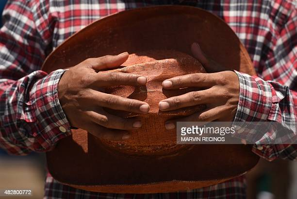 A cowboy holds his hat during the yearly rodeo to honor the Divine Savior of the World patron saint of the city in San Salvador on August 02 2015 AFP...