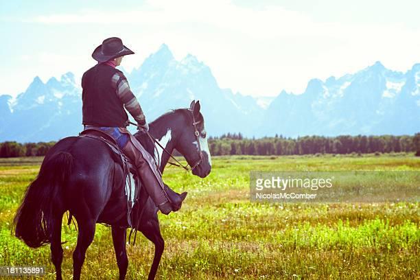 Cowboy horse riding towards the Rockies Grand Teton range
