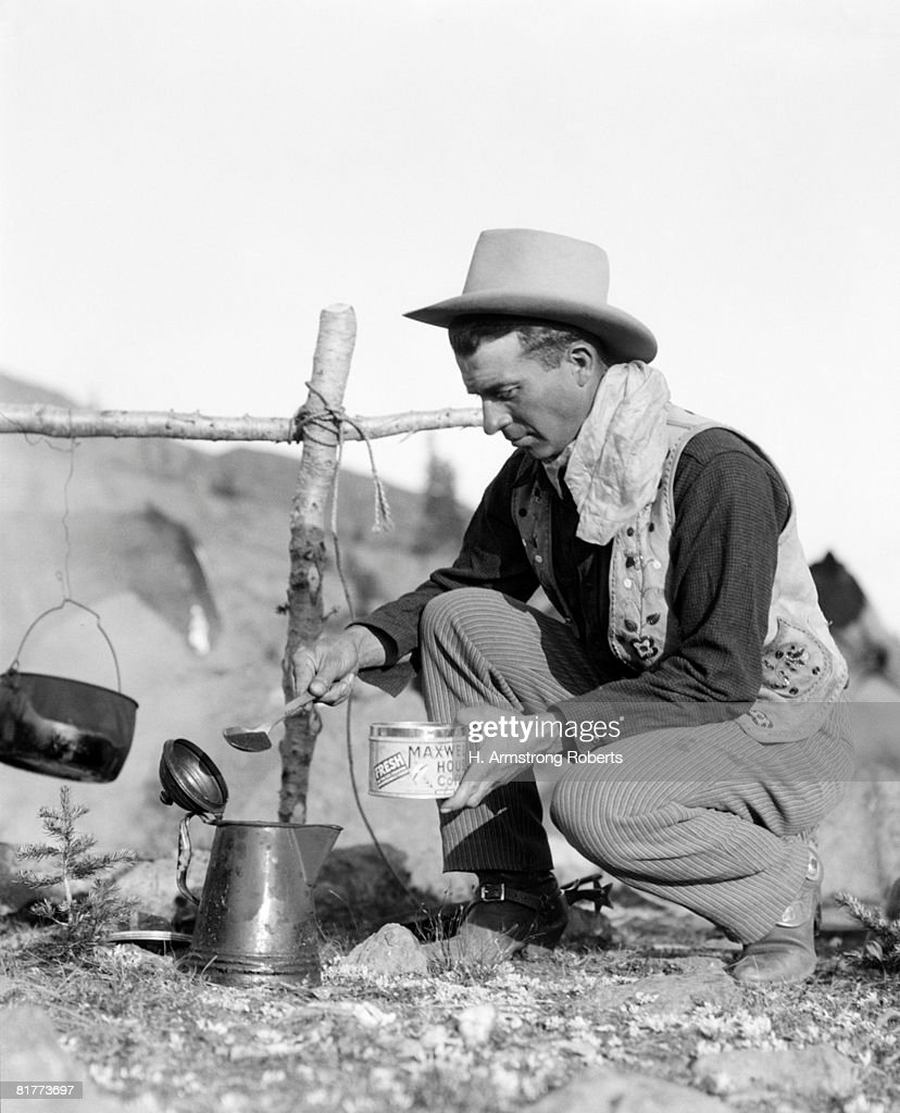 Cowboy kneeling by campfire, pouring coffee grounds into pitcher. : Stock Photo