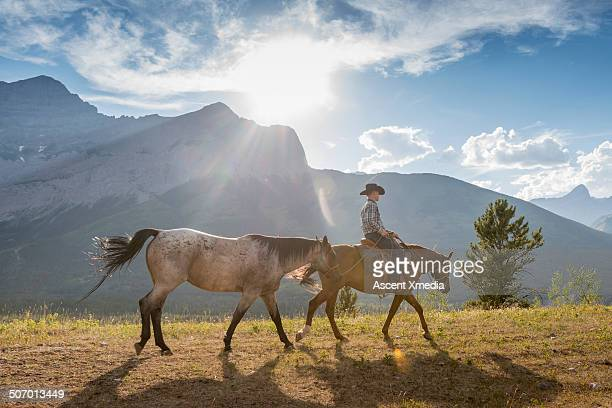 Cowboy leads horse across mountain rangeland