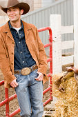 Cowboy leaning against fence, smiling, portrait