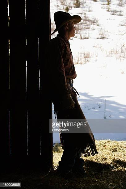 Cowboy Leaning in Doorway of Barn