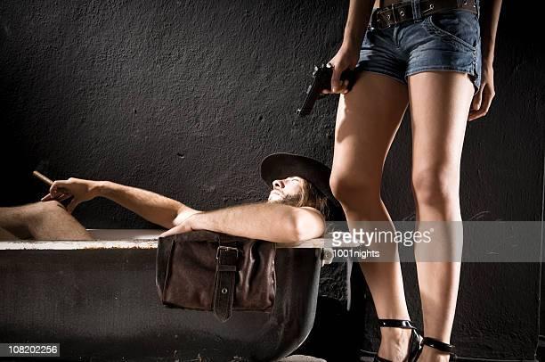 Cowboy Lying in Bathtub with Woman Holding Gun Near Him
