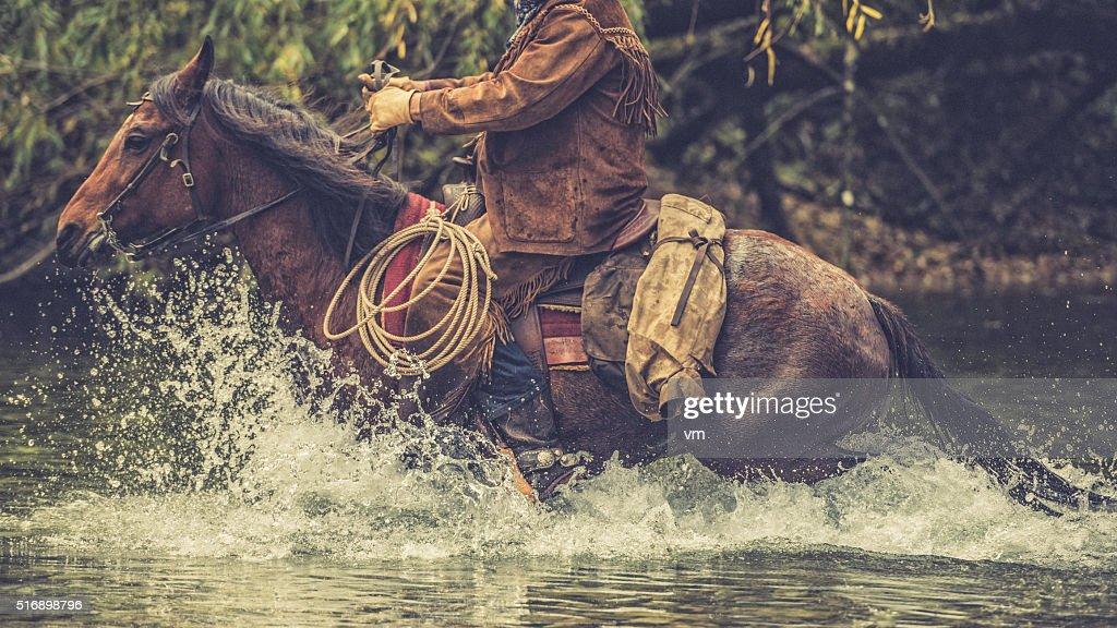 Cowboy on a horse riding across a river : Stock Photo