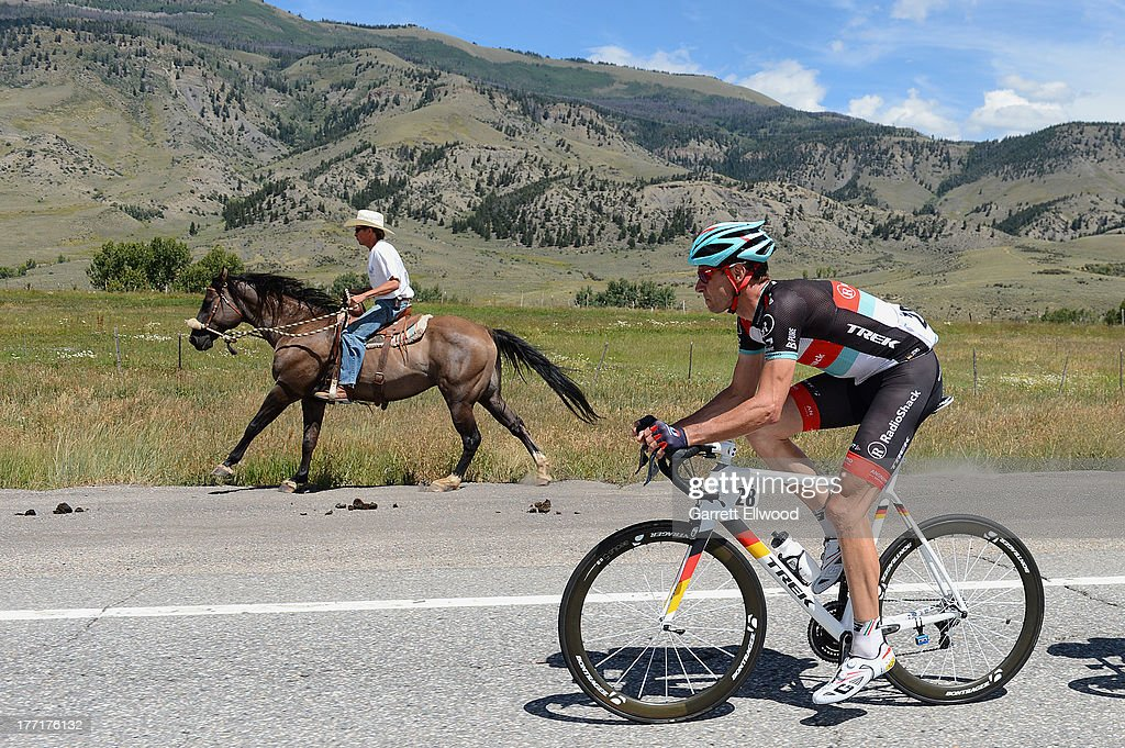 A cowboy races his horse with Jens Voigt #28 of Germany riding for RadioShack Leopard Trek between Breckenridge and Steamboat Springs during Stage Three of the USA Pro Cycling Challenge on August 21, 2013 in Steamboat Springs, Colorado. Copyright 2013 Copyright 2013
