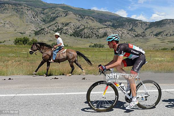 A cowboy races his horse with Jens Voigt of Germany riding for RadioShack Leopard Trek between Breckenridge and Steamboat Springs during Stage Three...