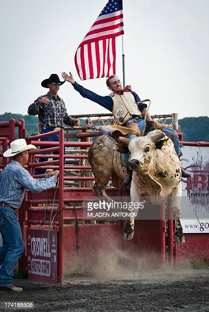 A cowboy rides a bull during 'Battle of the Beast' bull riding competition at J Bar W ranch in Union Bridge Maryland on July 20 2013 Professional...