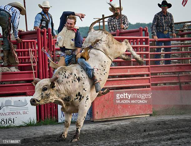 A cowboy rides a bull during the 'Battle of the Beast' bull riding competition at J Bar W ranch in Union Bridge Maryland on July 20 2013 Professional...